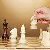 Chess board with chess pieces on brown background, © Africa Studio – Fotolia